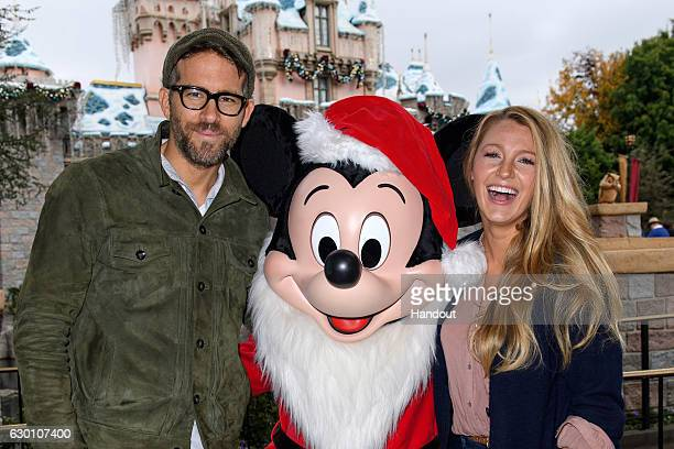 In this handout photo provided by Disney Parks Ryan Reynolds and Blake Lively meet Mickey Mouse at Sleeping Beauty's Winter Castle at Disneyland park...