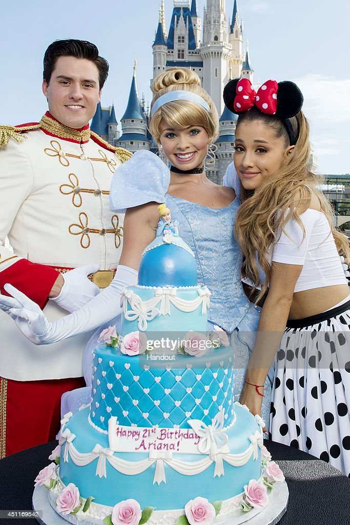 In this handout photo provided by Disney Parks, singer Ariana Grande (R) poses with Cinderella and Prince Charming in front of Cinderella Castle in the Magic Kingdom June 24, 2014 in Lake Buena Vista, Florida. Also pictured: Disney chefs created a four-tier birthday cake for Grande in Cinderella's favorite color, Bibbidi Bobbidi Blue. Grande is celebrating her 21st birthday with dozens of family and friends at Walt Disney World.