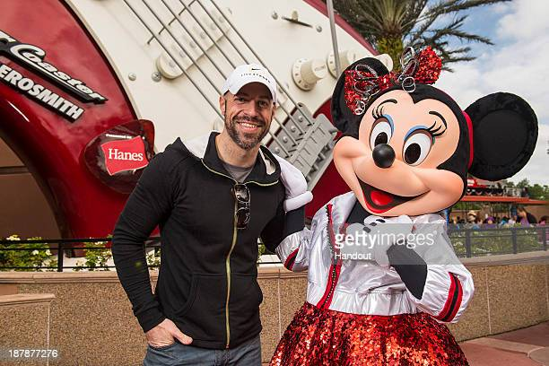 In this handout photo provided by Disney Parks singer/songwriter Chris Daughtry poses with Minnie Mouse in front of a giant electric guitar outside...