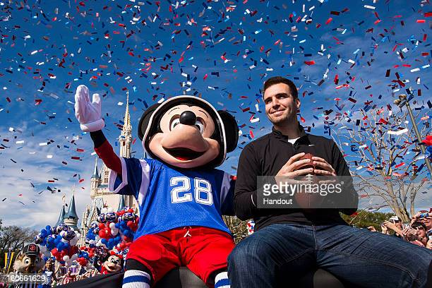 In this handout photo provided by Disney Parks Super Bowl XLVII MVP Joe Flacco rides with Mickey Mouse in a parade through the Magic Kingdom at Walt...