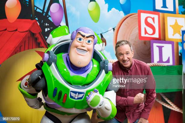 In this handout photo provided by Disney Parks Tim Allen strikes a pose with Buzz Lightyear after taping an interview for Toy Story Landexclusive...