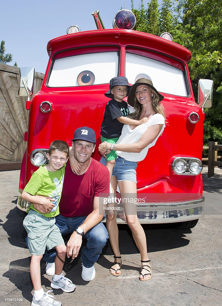 In this handout photo provided by Disney Parks, Tom Brady, his son Jack, 5, Gisele Bundchen, and their son Benjamin, 3, pose with Red the Fire Truck at Cars Land at Disney California Adventure park July 2, 2013 in Anaheim, California. The 12-acre Cars Land immerses guests in the thrilling world of the Disney-Pixar blockbuster 'Cars' film franchise as they step into the town of Radiator Springs.