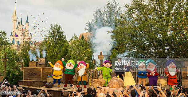 In this handout photo provided by Disney Parks Tom Staggs chairman of Walt Disney Parks Resorts joins Snow White the Seven Dwarfs to dedicate the...