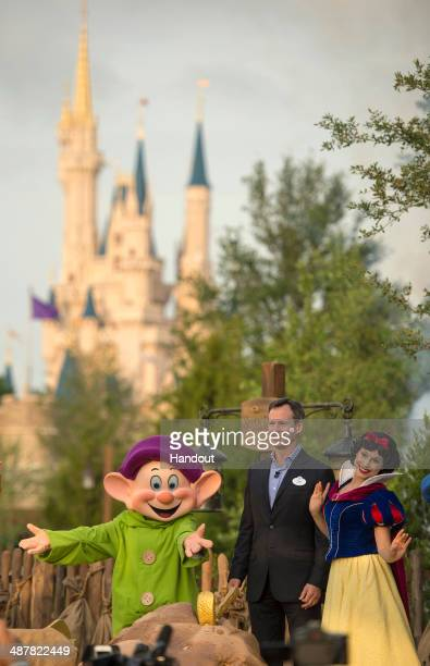 In this handout photo provided by Disney Parks Tom Staggs chairman of Walt Disney Parks Resorts joins Disney's Snow White and Dopey to dedicate the...