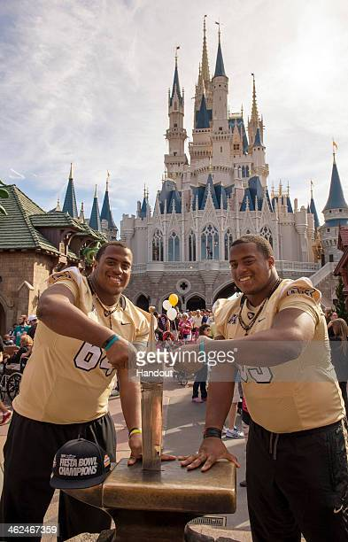 In this handout photo provided by Disney Parks University of Central Florida Knights offensive linemen Justin McCray and Jordan McCray pull the...