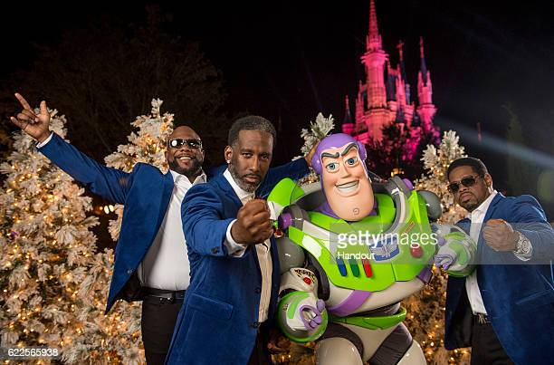 In this handout photo provided by Disney Parks Wanya Morris Shawn Stockman and Nathan Morris of RB group Boyz II Men pose with Buzz Lightyear during...