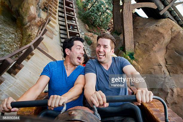 In this handout photo provided by Disney Resorts HGTVs The Property Brothers Drew Scott and Jonathan Scott ride the Seven Dwarfs Mine Train...
