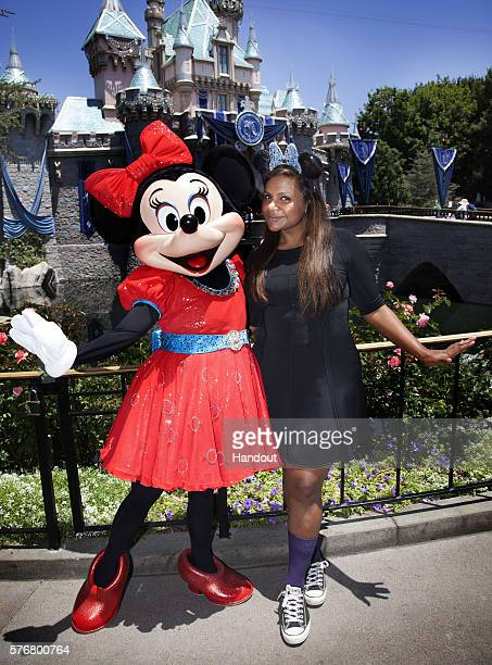 In this handout photo provided by Disney Resorts Mindy Kaling celebrates her first visit to the Disneyland Resort with Minnie Mouse outside of...
