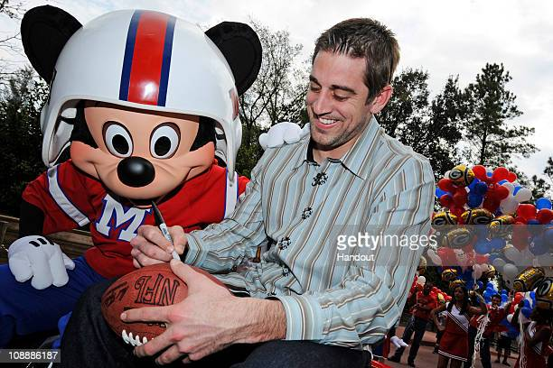 In this handout photo provided by Disney Super Bowl XLV Most Valuable Player Aaron Rodgers signs a football during a celebratory ride with Mickey...