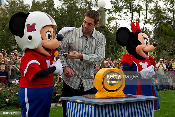 In this handout photo provided by Disney Super Bowl XLV Most Valuable Player Aaron Rodgers offers Mickey Mouse a bite of Wisconsin cheddar cheese at...