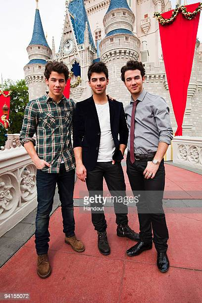 In this handout photo provided by Disney The Jonas Brothers Nick Jonas Joe Jonas and Kevin Jonas pose in front of Cinderella Castle at the Magic...