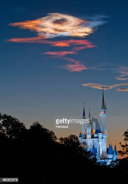 In this handout photo provided by Disney the sunrise over Cinderella Castle in the Magic Kingdom creates a multicolored effect in the sky as the sun...