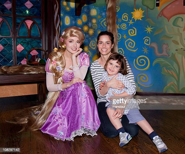 In this handout photo provided by Disneyland actress Amanda Peet and her daughter Frances Benioff meet Rapunzel from the Disney animated film...