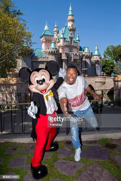 In this handout photo provided by Disneyland Resort actor Jamie Foxx meets Mickey Mouse in front of the Sleeping Beauty Castle on July 3 2017 at...