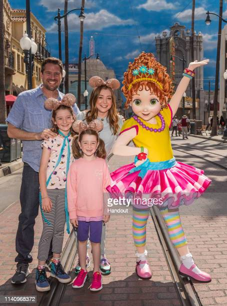 In this handout photo provided by Disneyland Resort actress Alyson Hannigan her husband Alexis Denisof daughters Satyana and Keeva pose with Disney...