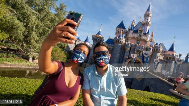 In this handout photo provided by Disneyland Resort, Guests pose in front of Sleeping Beauty Castle at the Disneyland Resort on April 30, 2021 in...
