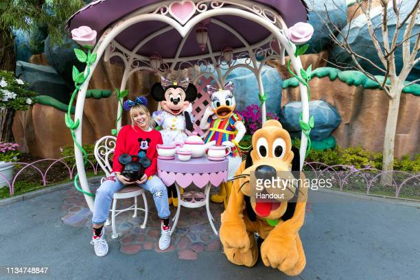 In this handout photo provided by Disneyland Resort Musician Miley Cyrus poses with Minnie Mouse Daisy Duck and Pluto during Get Your Ears On A...