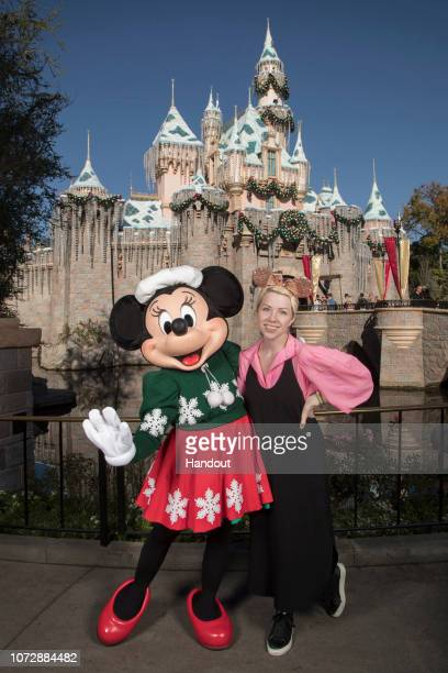 In this handout photo provided by Disneyland Resort singersongwriter Carly Rae Jepsen poses with Minnie Mouse in front of Sleeping Beautys Winter...