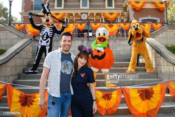 In this handout photo provided by Disneyland Resorts, Jonathan Scott and Zooey Deschanel pose with Goofy, Donald and Pluto in their Halloween finest...