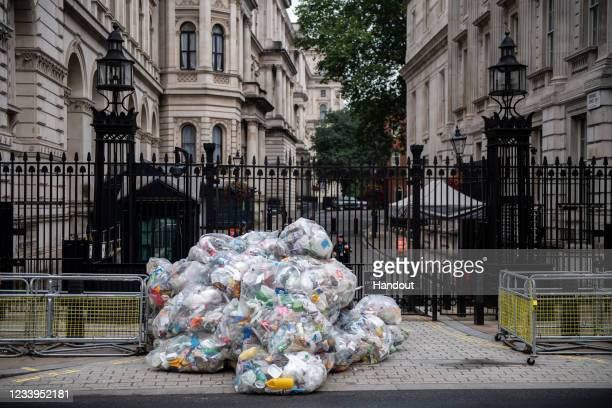 In this handout photo provided by Greenpeace, Greenpeace activists dump bags of plastic waste at the main entrance to Downing Street in a protest...