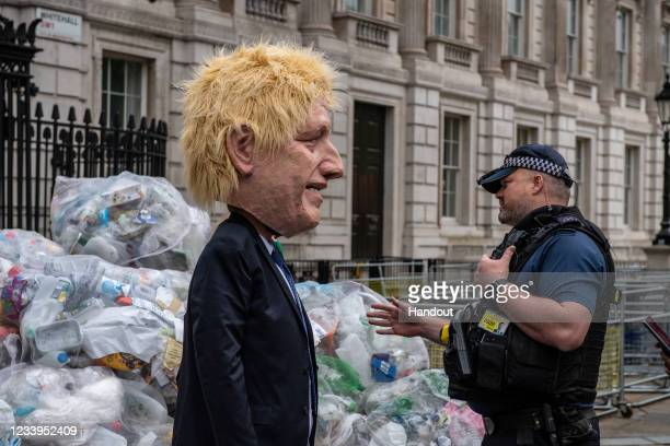 In this handout photo provided by Greenpeace, Police officers speak to a Greenpeace activist dressed as Boris Johnson in a protest against the UK...