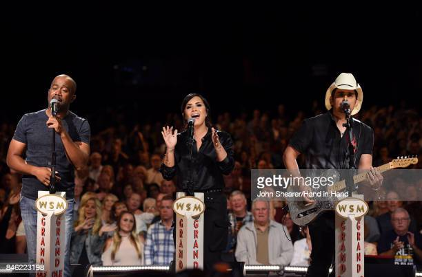 In this handout photo provided by Hand in Hand Darius Rucker Demi Lovato and Brad Paisley perform onstage during Hand in Hand A Benefit for Hurricane...