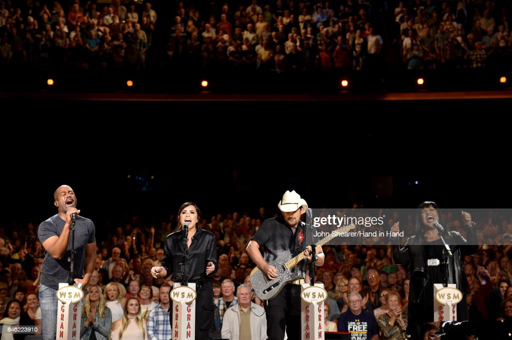 In this handout photo provided by Hand in Hand, Darius Rucker, Demi Lovato, Brad Paisley, and CeCe Winans perform onstage during Hand in Hand: A Benefit for Hurricane Relief at the Grand Ole Opry House on September 12, 2017 in Nashville, Tennessee.