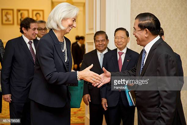 In this handout photo provided by IMF International Monetary Fund Managing Director Christine Lagarde shakes hands with Prime Minister Hun Sen at the...