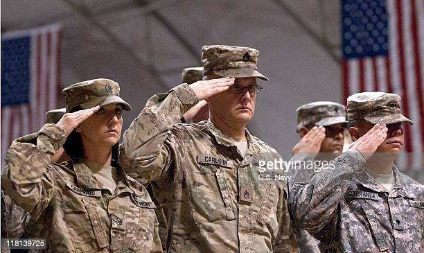 In this handout photo provided by ISAF Regional Command service members salute after US Army Gen David H Petraeus commanding general of the NATO...