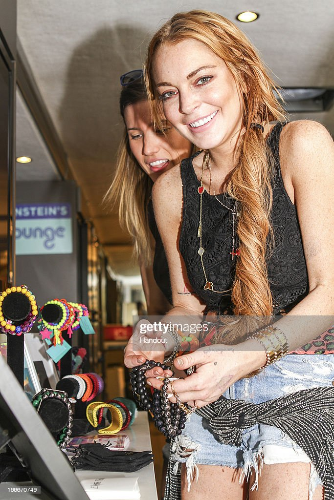 In this handout photo provided by Kari Feinstein PR, Lindsay Lohan holding Elecrtic Picks, and looking at Rock On and Fabio V. attends the Kari Feinstein's style lounge on the road in the desert April 14, 2013 near Indio, California.