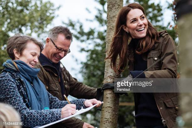 In this handout photo provided by Kensington Palace Catherine Duchess of Cambridge with Andree Davies and Adam White of Davies White Landscape...