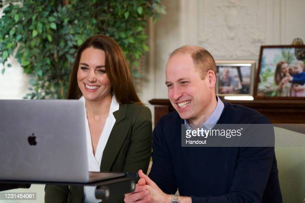 In this handout photo provided by Kensington Palace, Prince William, Duke of Cambridge and Catherine, Duchess of Cambridge speak with two families...