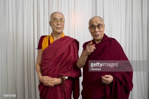 In this handout photo provided by Madame Tussauds His Holiness the Dalai Lama visits Madame Tussauds and poses with a wax figure of himself on June...