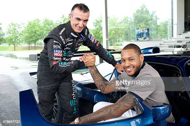 In this handout photo provided by Maserati Pro racecar driver Andrea Bertolini visits with New York Knicks basketball player and NBA AllStar Carmelo...