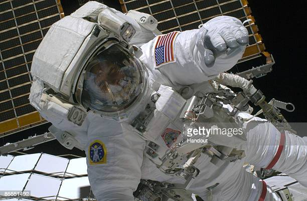 In this handout photo provided by NASA Astronaut Steve Swanson STS119 mission specialist participates in the mission's first scheduled session of...