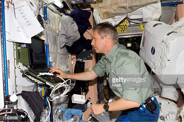 In this handout photo provided by NASA, European Space Agency astronaut Thomas Reiter of Germany uses a computer in the Unity node of the...