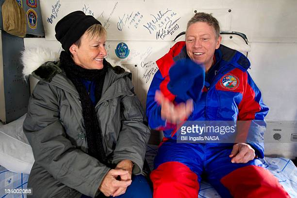 In this handout photo provided by NASA Expedition 29 Commander Mike Fossum right tosses his hat into the air and comments to Peggy Whitson NASA Chief...