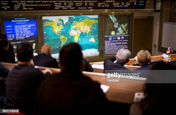 In this handout photo provided by NASA Friends and family members of the Soyuz MS07 crew watch a live view of the International Space Station as seen...