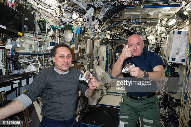 In this handout photo provided by NASA NASA astronaut Scott Kelly gives a thumbs up on the quality of his snack while taking a break from his work...