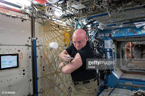 In this handout photo provided by NASA NASA astronaut Scott Kelly gives himself a flu shot for an ongoing study on the human immune system September...