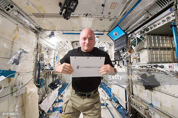 In this handout photo provided by NASA NASA astronaut Scott Kelly is photographed in the Japanese Experiment Module holding a sign with the hashtag...