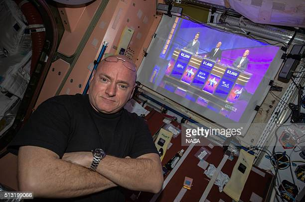 In this handout photo provided by NASA, NASA astronaut Scott Kelly watches his twin brother former astronaut Mark Kelly on Celebrity Jeopardy May 15,...