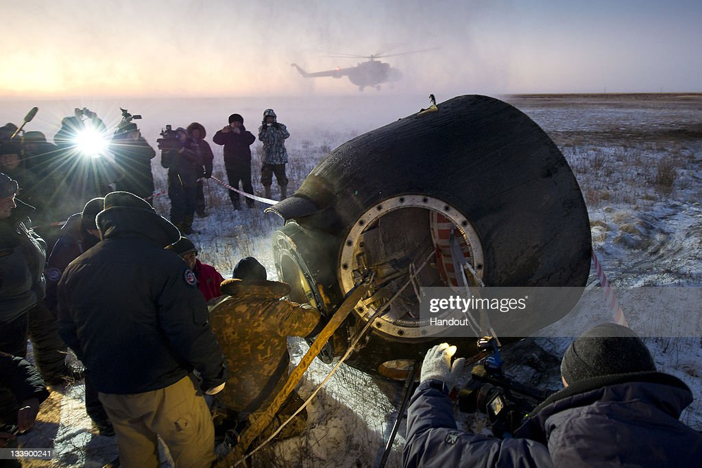 In this handout photo provided by NASA, Russian support personnel work to help get Expedition 29 crew members out of the Soyuz TMA-02M spacecraft shortly after the capsule landed with Expedition 29 Commander Mike Fossum, and Flight Engineers Sergei Volkov and Satoshi Furukawa on November 22, 2011 outside of the town of Arkalyk, Kazakhstan. NASA Astronaut Fossum, Russian Cosmonaut Volkov and JAXA (Japan Aerospace Exploration Agency) Astronaut Furukawa are returning from more than five months onboard the International Space Station (ISS) where they served as members of the Expedition 28 and 29 crews.