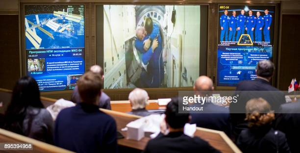 In this handout photo provided by NASA Scott Tingle of NASA is seen embracing Expedition 54 Commander Alexander Misurkin after the opening of the...