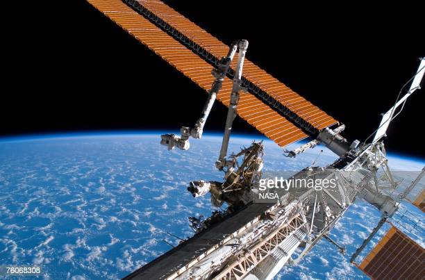 In this handout photo provided by NASA, the Canadarm2 and solar array panel wings on the International Space Station are extended during the...