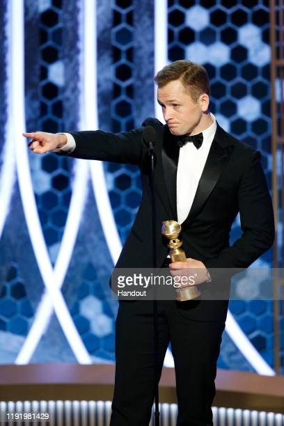In this handout photo provided by NBCUniversal Media LLC Taron Egerton accepts the award for BEST PERFORMANCE BY AN ACTOR IN A MOTION PICTURE MUSICAL...