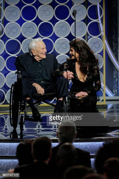 In this handout photo provided by NBCUniversal Presenters Kirk Douglas and Catherine Zeta Jones speak onstage during the 75th Annual Golden Globe...