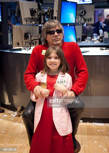 In this handout photo provided by NYSE Euronext MakeAWish Child Katherine Mara from The MakeAWish Foundation of Connecticut poses with musician Jose...