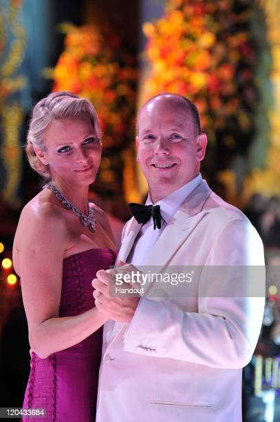 In this handout photo provided by Realis/SBM Princess Charlene of Monaco and Prince Albert II of Monaco dance during the 63rd Red Cross Ball at the...