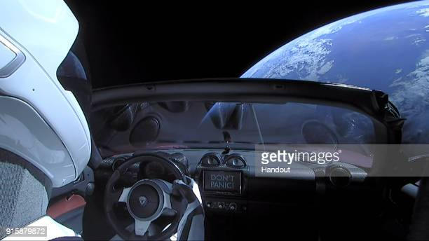 "In this handout photo provided by SpaceX, a Tesla roadster launched from the Falcon Heavy rocket with a dummy driver named ""Starman"" heads towards..."